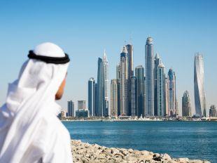DUBAI, UAE - NOVEMBER 7: Modern buildings in Dubai Marina, on November 7, 2013, Dubai, UAE. In the city of artificial channel length of 3 kilometers along the Persian Gulf. Man in Arab dress looks at the city