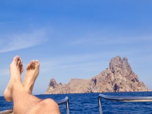 Ibiza relaxed Es Vedra boat bow view with crossed man legs and feet