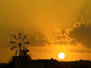 Sunset on the island of Mallorca, the sun setting behind one of the may windmills on the island.